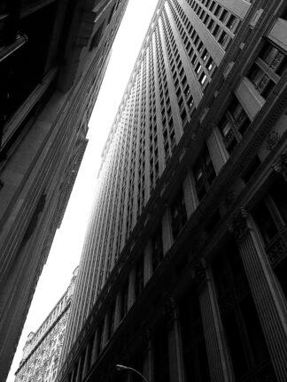 Svartvitt foto på en glugg av himmel mellan två skyskrapor.
